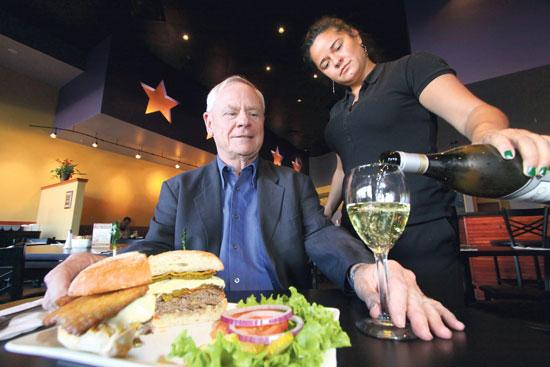 5 Star Burgers founder Bob Gontram enjoys a burger and wine poured by Kristina Vincenty, the NE Heights restaurant's manager.