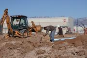 Workers prepare Mesa del Sol development land for model home foundations for Rachel Matthews Homes. In the background are Albuquerque Studios' soundstages.