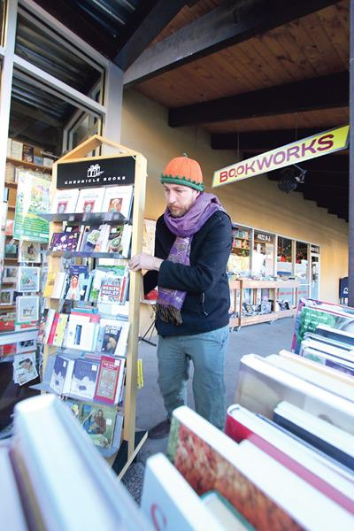 Bookworks co-owner Wyatt Wegrzyn moves books and other store products outdoors in front of his bookstore's windows on a recent chilly morning. Wegrzyn and some others in New Mexico believe online retailers should operate under the same sales tax rules as businesses that have a physical presence.