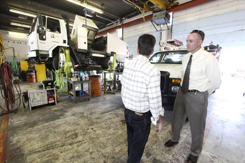 N.M. DOT Training Manager Joaquian Nielsen, right, and Equipment Manager Ray Waggerman swap observations about DOT's fleet at the N.M. DOT District 3 mechanic shop in Albuquerque.