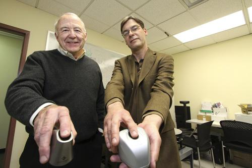 Lumidigm CEO Bob Harhour (left) and CTO Robert Rowe display two generations of the company's fingerprint scanning devices.