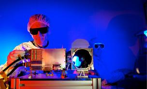 Los Alamos National Laboratory's Roger Wiens removes a laser safety plug on the ChemCam Mast Unit, which was chosen for the Mars rover Curiosity. Bruce Barraclough mans a console.