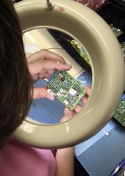 A Lectrosonics employee examines a circuit board produced at the Rio Rancho plant.