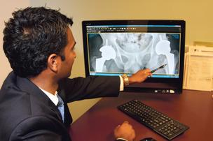 New Mexico Orthopaedics physician Krishna Tripuraneni studies a patient's hip replacement X-ray.
