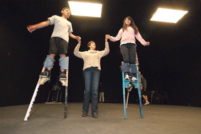 Working Classroom Executive Director Nan Elsasser, center, helps David De La Cruz, 12, and Martha Diaz, 13, walk on stilts at the group's new facility.