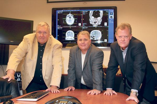 Medical images from Alta Vista Regional Medical Center appear behind (left) NM Software President and CEO Dick Govatski, and neurologists David McCraney and (right) John Tanner