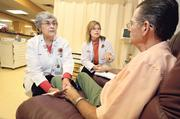 From left, registered nurse Rose Reese and physician assistant Mikal Smoker meet with patient Regis H. Cassidy, who is being treated for multiple myeloma at the UNM Cancer Center.