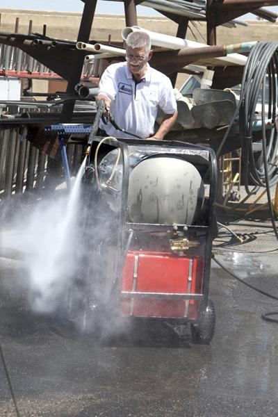 Aamerican Powerwash Equipment and Supplies LLC co-owner Mike Schramski tests the performance of a pressure washer at the company's Albuquerque office.
