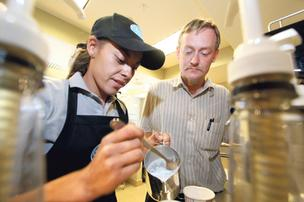 St. Martin's Hospitality Center Training Manager Tyler Tencza, right, instructs counter server Erica Tafoya at the nonprofit's new coffee shop Downtown.