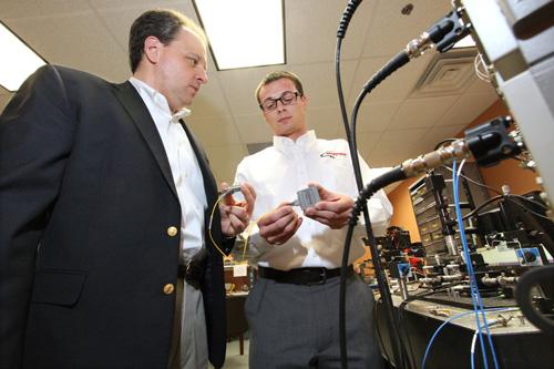 Skorpios President and CEO Stephen Krasulick, left, and Research Engineer Chris Blivin examine optical wafers made with Skorpios' technology. Skorpios developed this device, called a tuner laser evaluation board, to test and evaluate the company's water, inserted on the far-left edge.