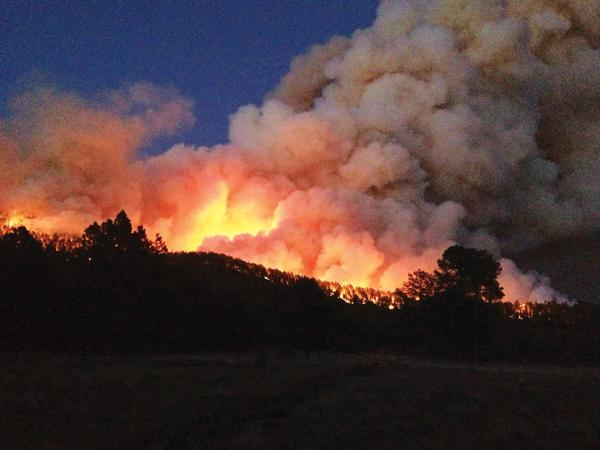Fires in New Mexico this summer, like the Thompson Ridge Fire, pictured, have complex effects on tourism. As firefighters swoop in, they can boost local taxes and wages, but some people won't visit if a fire is nearby.