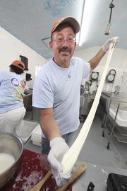 Old Windmill's Ed Lobaugh stretches a piece of mozzarella cheese. The Estancia-area dairy, which opened in 2007, produces 13 flavors of chevre (soft goat cheese), blue cheese and feta from goat milk, and semi-hard and cream cheese from cow milk.