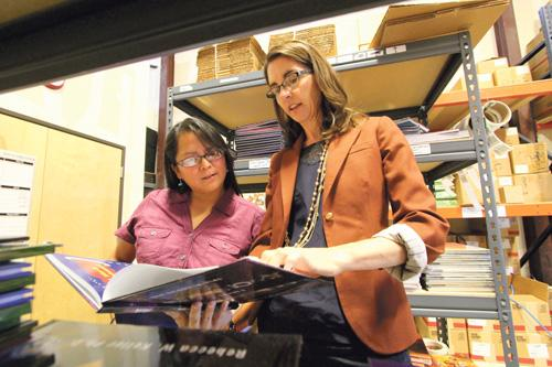 Rebecca Keller of Gravitas Publications, right, speaks with customer Viana Sikes at the company's warehouse. After winning a business pitch competition, Keller's goal is to reach $1 million in revenue with her company in the next 18 months.