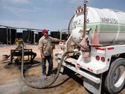 A 5,000-gallon truck unloads produced water for reinjection underground at a facility in Jal. Dozens of trucks use the facility daily.