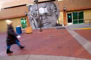 Artist Chip Thomas recreated his wheat paste mural of a boy with binoculars at the new offices for Creative Albuquerque on the 4th Street Mall. Thomas, a doctor on the Navajo Nation, creates large murals from photos.