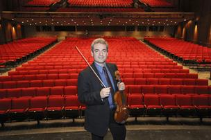 Marian Tanau, the New Mexico Philharmonic's executive director, is a violin player with a head for business. Here, he's pictured at Popejoy Hall in Albuquerque. He commutes between Michigan and Albuquerque to run the Philharmonic.