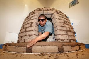 Wesley Valencia works on replicating a traditional horno oven at the Indian Pueblo Cultural Center's Centennial exhibit, which explores the impacts that state and federal  policy have had on pueblos in New Mexico.