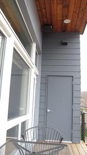 This overhang on the upper level porch shades TrekHaus windows in summer to keep the temperatures indoors from becoming too warm. Behind the door at end is a storage closet that houses the Zehnder ComfoAir 350 heat recovery ventilator. Note the hatch in the roof, which accesses a solar array above.
