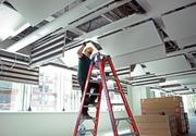 Chris Cirlincrone of Dynalectric Co. wires light sensors in an office space in the Edith Green-Wendell Wyatt federal office building. In this image, coils are visible in the ceiling panels. The water-based system will reduce ambient noise in the building and is very energy efficient.