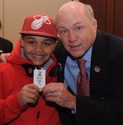 Eight-year-old Bryson Jackson (son of Daphne Bryson Jackson, principal with GovLink Inc.) gets a Chick-fil-A coupon from Dan Cathy, president of Chick-fil-A Inc. Chick-fil-A is a sponsor of the College Football Hall of Fame.
