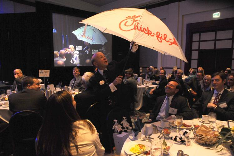 Chick-fil A Inc. President Dan Cathy, keynote speaker at Pacesetters, shows the audience how the fast-food chain greets customers who come when it's raining.