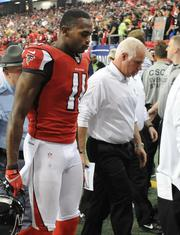 Falcons wide receiver Julio Jones and head coach Mike Smith head to the locker room at halftime looking concerned.