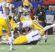 An LSU player loses his lid as he and some teammates go for a fumble recovery.