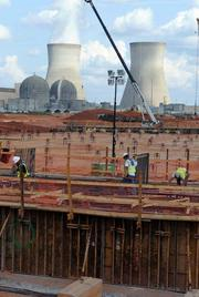 Workers prepare the base of the cooling towers for its concrete pour. Rebar and forms are set in place after all of the underground pipes were installed.