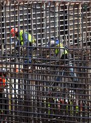 Workers tie in rebar as they prepare it for the concrete pour.