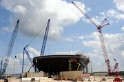 Several cranes surround the Plant Vogtle construction site. Work on the containment vessel foreground continues.