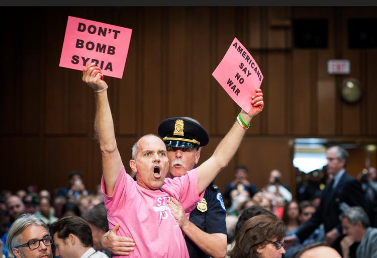 "An activist with the Code Pink group disrupts a Senate Foreign Relations Committee hearing on Syria in Washington, D.C., U.S., on Tuesday, Sept. 3, 2013. U.S. Secretary of State John Kerry told lawmakers that President Obama ""has no intention"" of putting American troops on the ground in Syria."