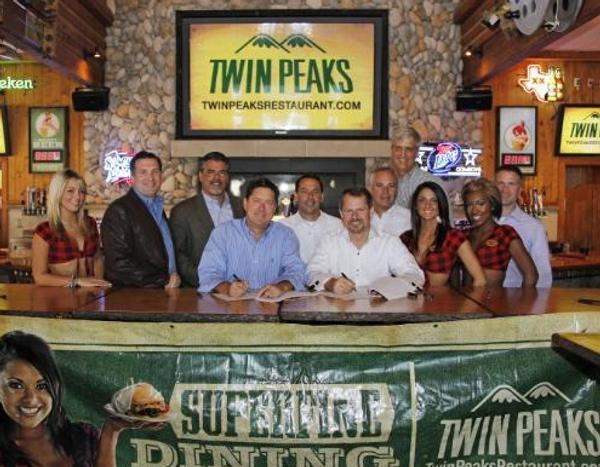 Twin Peaks announced an investment group led by top former Hooters executives has signed a series of development agreements to open 35 Twin Peaks restaurants throughout six states. Seated from left, Randy DeWitt, Twin Peaks Co-Founder and CEO, Seated right, Coby Brooks, La Cima Restaurants and former Hooters CEO; Standing from left, Jack Gibbons, Scott Gordon, Joe Hummel, Roger Gondek, Jim Tessmer, and Clay Mingus.