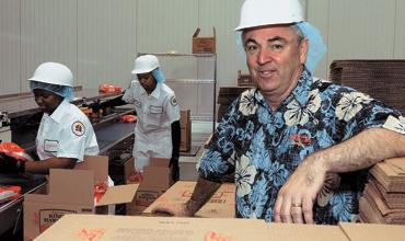 Plant open: John Linehan, executive vice president of King's Hawaiian, oversees a line of baked goods at the company's new plant in Oakwood in Hall County. The 115,000-square-foot facility, where King's Hawaiian baked goods are produced, opened in March.