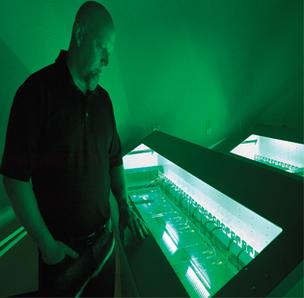 Midas Networks COO Kenneth Tooke monitors servers submerged in oil, which cools electronics more efficiency than air.
