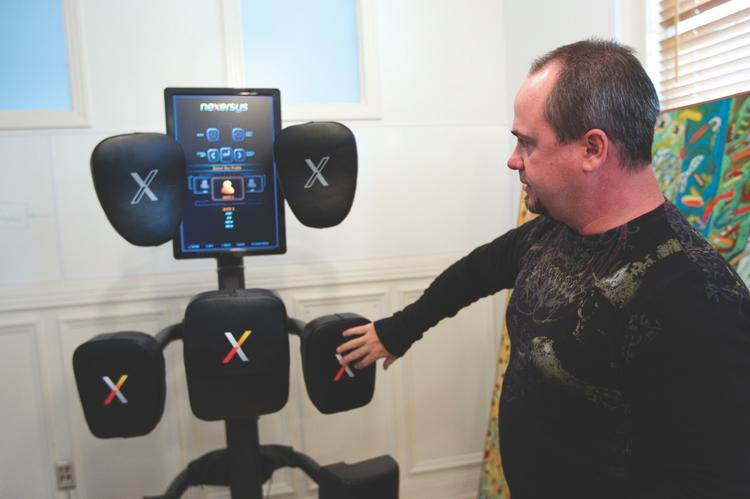 Nexersys Chief Marketing Officer Craig Gatzlaff shows off his company's workout machine, which will retail for about $2,495.