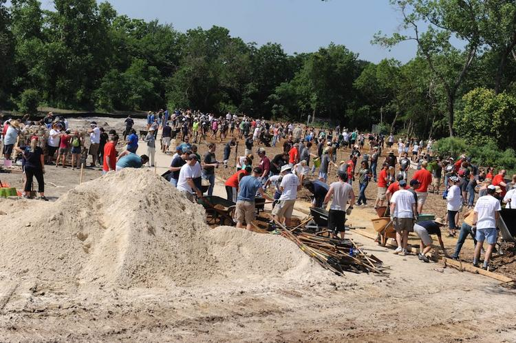 About 600 volunteers broke a sweat and turned some dirt at the site of Sustainable Food Center's future community garden at the MLK Rail Station.