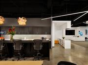 The office is designed around a spacious gourmet kitchen that includes a 20-foot communal table for employee gatherings. The unconventional light fixtures are constructed of curved wood.