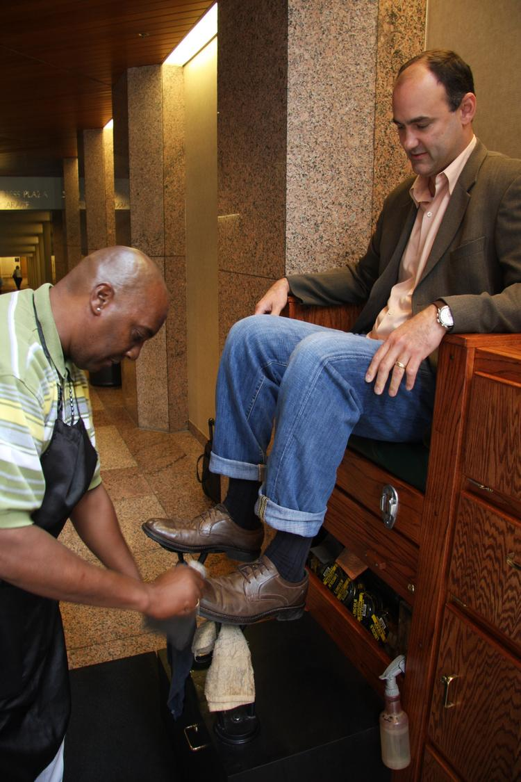 Shiny Shoes' Shedric Jones polishes a customers shoes at his stand at 111 Congress Ave.