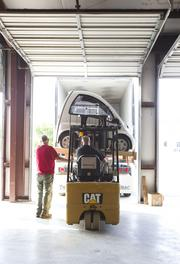 Workers load the first Kenguru into a shipping container so it can make its way to a dealership in France.