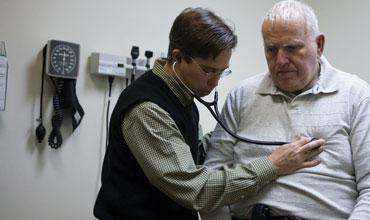 Dr. Peter Nutson examines patient Joe Irving at WellMed.