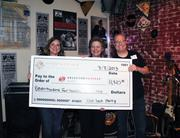 Dress for Success leaders Mia Johns (left) and Judy Chambers help HT Staffing CEO Mark Turpin hold up a big check after a March 8 fundraiser.