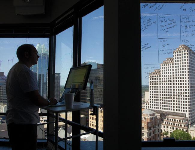Ian Ragsdale, a freelance technology consultant, works at Austin TechLive while looking over the skyline in downtown Austin.