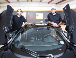 Jacob White (left) and Justin Blackburn show off a McLaren at their headquarters. It's one of many exotic cars Austinites can get a taste of if they don't want to fully own one.