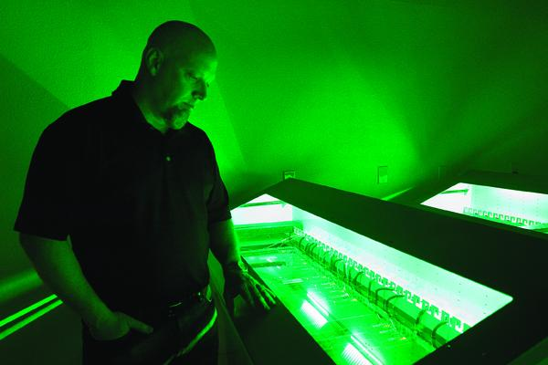 Midas Networks Chief Operating Officer Kenneth Tooke monitors  servers submerged in oil, which cools electronics more effiiciently than air.