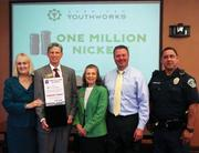 """From left: IBC Bank-Austin First Vice President Deborah Portman, American YouthWorks CEO Parc Smith, American YouthWorks Board President Margarine Beaman, IBC Bank Vice President Shawn Stewart and Austin police officer Willie Torres kick off the """"One Million Nickels"""" initiative, with donations being accepted at IBC branches through April 9."""