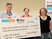 Realty Austin co-owner Jonathan Boatwright presents a $65,000 check to Habitat for Humanity.