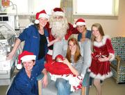 Nurses, along with new mother Rachelle Phillips and her 6-week old daughter Juliet, celebrate the holidays in the neonatal intensive care unit at St. David's Women's Center of Texas. Staff members dressed up as Santa and his helpers, took photos with the infants and also made keepsake ornaments with each baby's footprint.