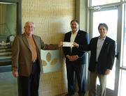 From left: PeopleFund CEO Gary Linder accepts a $5,000 donation from Texas Capital Bank's Robert Franco and Mike McConnel — one of the bank's many charitable acts this season.