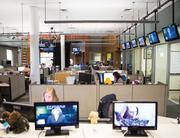 Television monitors line the perimeter of YNN's newsroom.