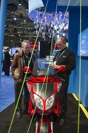 John Tittle, right, with Current Motor Co. explains the computer technology used in the red scooter pictured here to Mike Patton with Helca Mining Co.